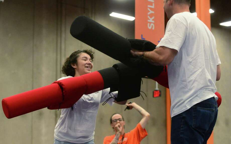 Norwalk police officer Gabriel DeMott, right, and members of the youth group under the umbrella of Juvenile Review Board, including Nayeli Rivera, participate in activities at Sky Zone as part of a mentoring program between police and kids. Photo: Erik Trautmann / Hearst Connecticut Media / (C)2016, The Connecicut Post, all rights reserved