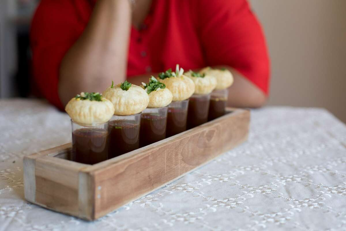 Priti Narayanan of Koolfi Creamery with her ice cream gol gappa, also known as pani puri filled with mango ice cream, shredded tart green apple and chopped cilantro, and dips it in a spicy, sweet tamarind water at her home on July 31, 2019 in San Leandro, California.
