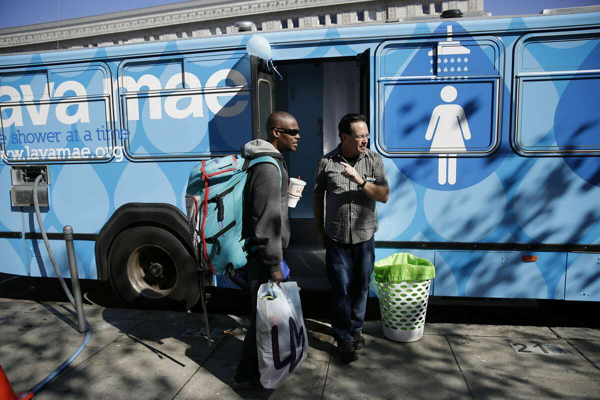 Raymond Thompson (l to r), who is homeless, is assisted by Michael McMorrow, mobile services manager, before taking a shower in the Lava Mae bus, on Tuesday, September 8, 2015 in San Francisco, Calif. Thompson says there aren't that many resources for people to clean up and that it gives people their privacy so that one doesn't have to be out in the open.