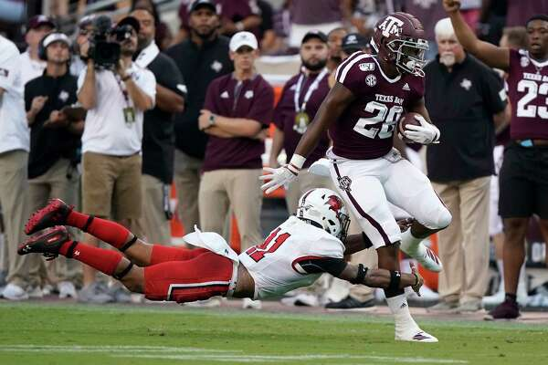 Texas A&M running back Isaiah Spiller (28) is tripped up by Lamar defensive back Cameron Hayes (11)after a first down run during the first half of an NCAA college football game, Saturday, Sept. 14, 2019, in College Station, Texas. (AP Photo/Sam Craft)