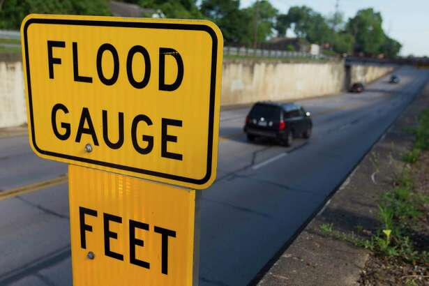 Vehicles pass by a flood gauge along a portion of North Frazier Street near McDade Street, an area known for flooding in heavy rain.