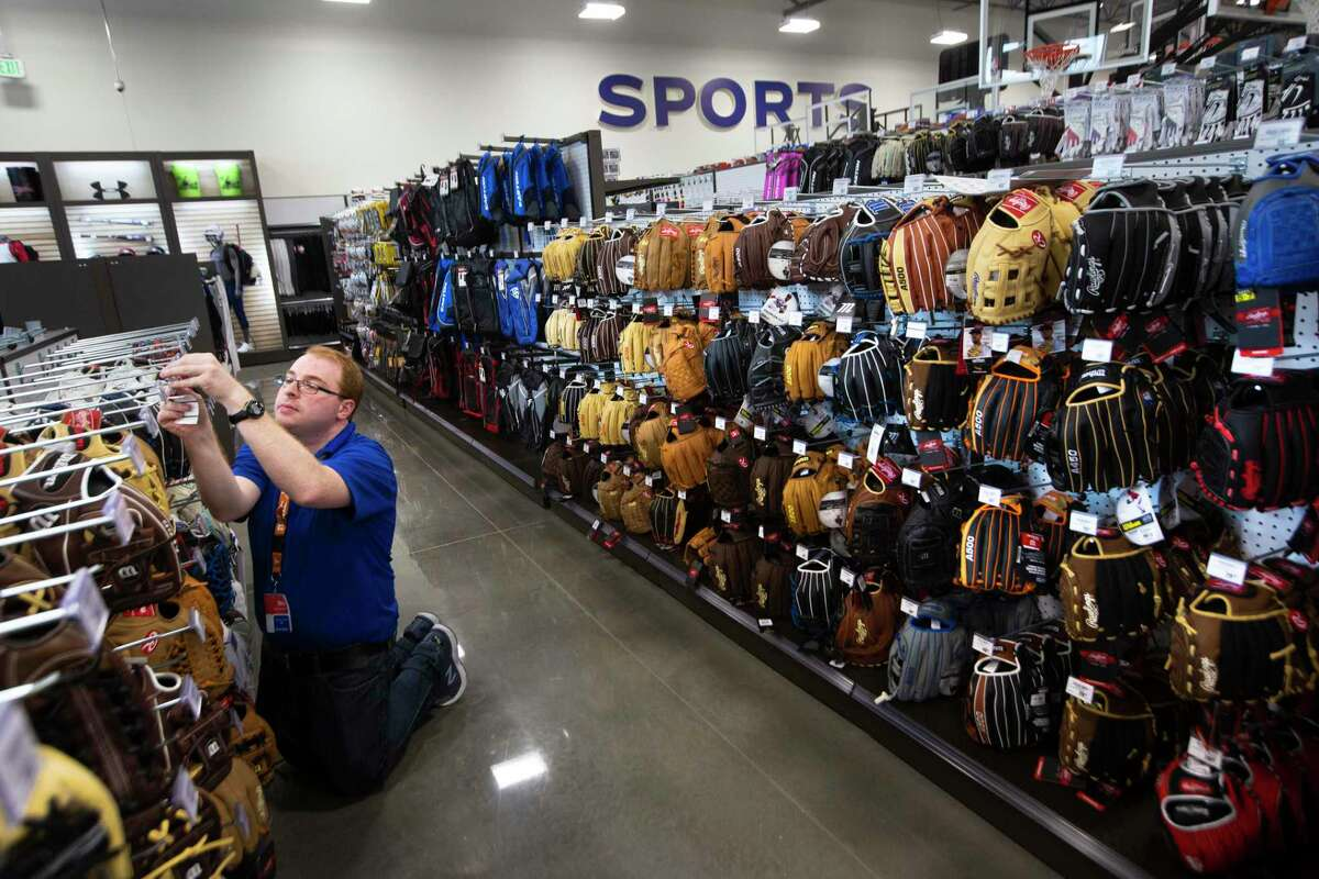 Rhi Bigner prices baseball gloves a few days before the grand opening of the sports store Academy in Richmond on Friday, Sept. 13, 2019.