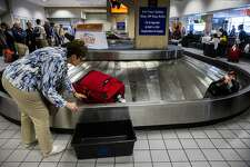 A traveler reaches for her bag as luggage moves around a baggage claim at Gate C on Friday, March 10, 2017 at DFW international Airport in Dallas. (Ashley Landis/The Dallas Morning News/TNS)