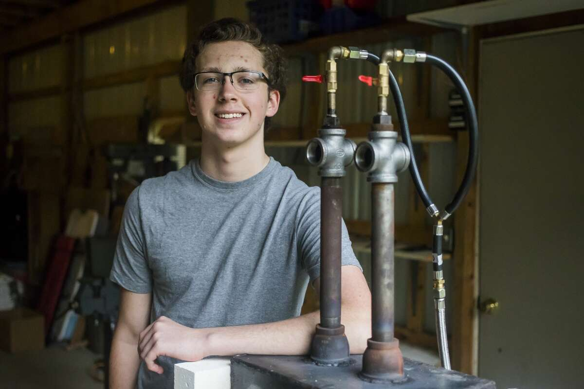 Kristopher Mercy of Sanford, 17, poses for a portrait alongside his forge, which he crafted himself, on Tuesday, Sept. 10, 2019 in his mother's garage. (Katy Kildee/kkildee@mdn.net)