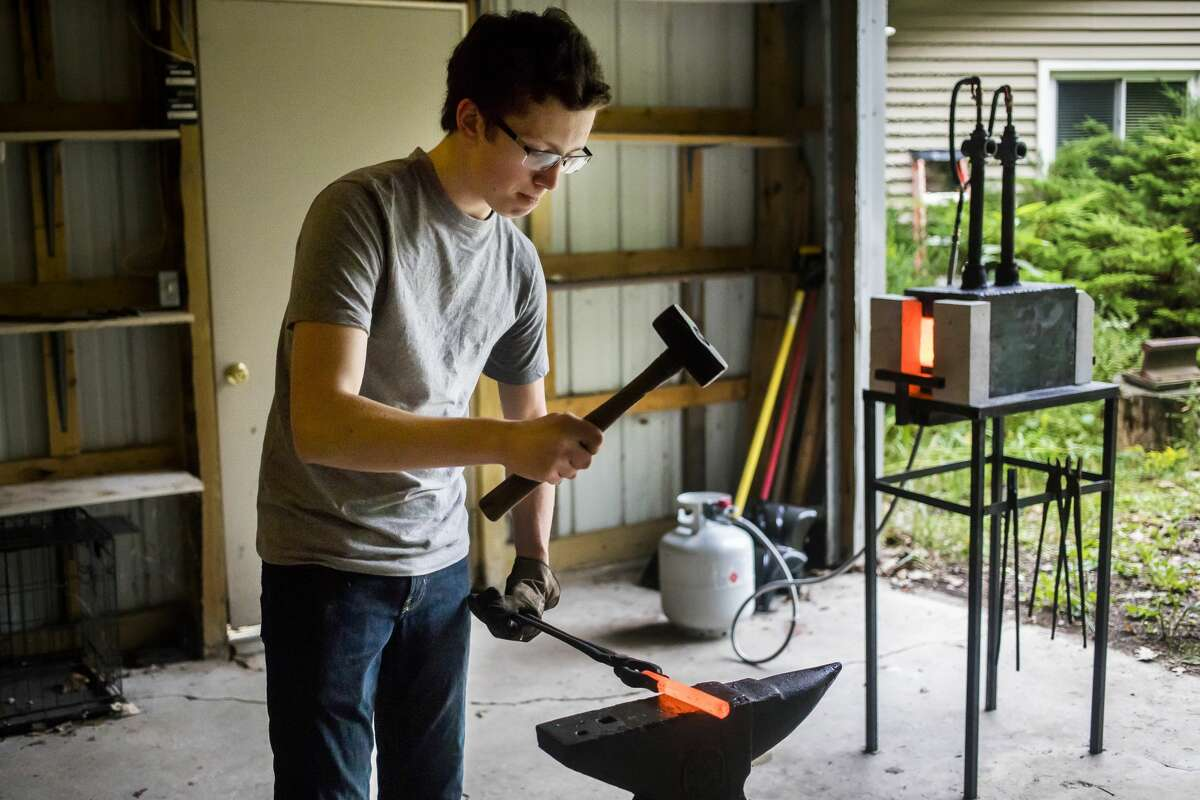 Kristopher Mercy of Sanford, 17, shapes a piece of metal after heating it inside his forge, which he crafted himself, on Tuesday, Sept. 10, 2019 in his mother's garage. (Katy Kildee/kkildee@mdn.net)