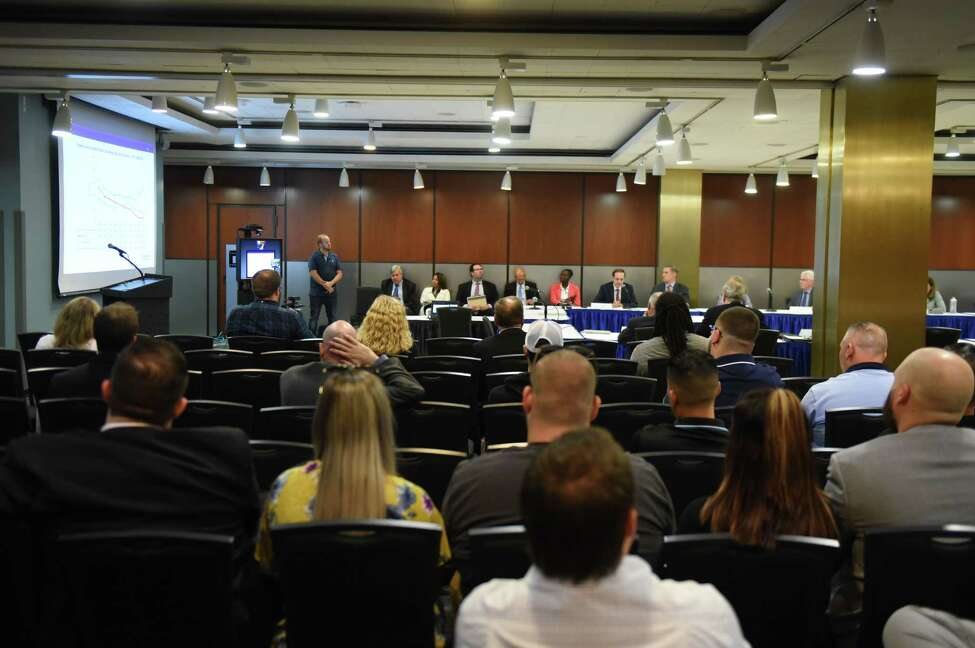 Audience members listen during a meeting of the state Public Health and Health Planning Council to vote on provisions to ban the sale of flavored e-cigarettes on Tuesday, Sept.17, 2019, at the Empire State Plaza Convention Center in Albany, N.Y. Gov. Andrew Cuomo announced Sunday