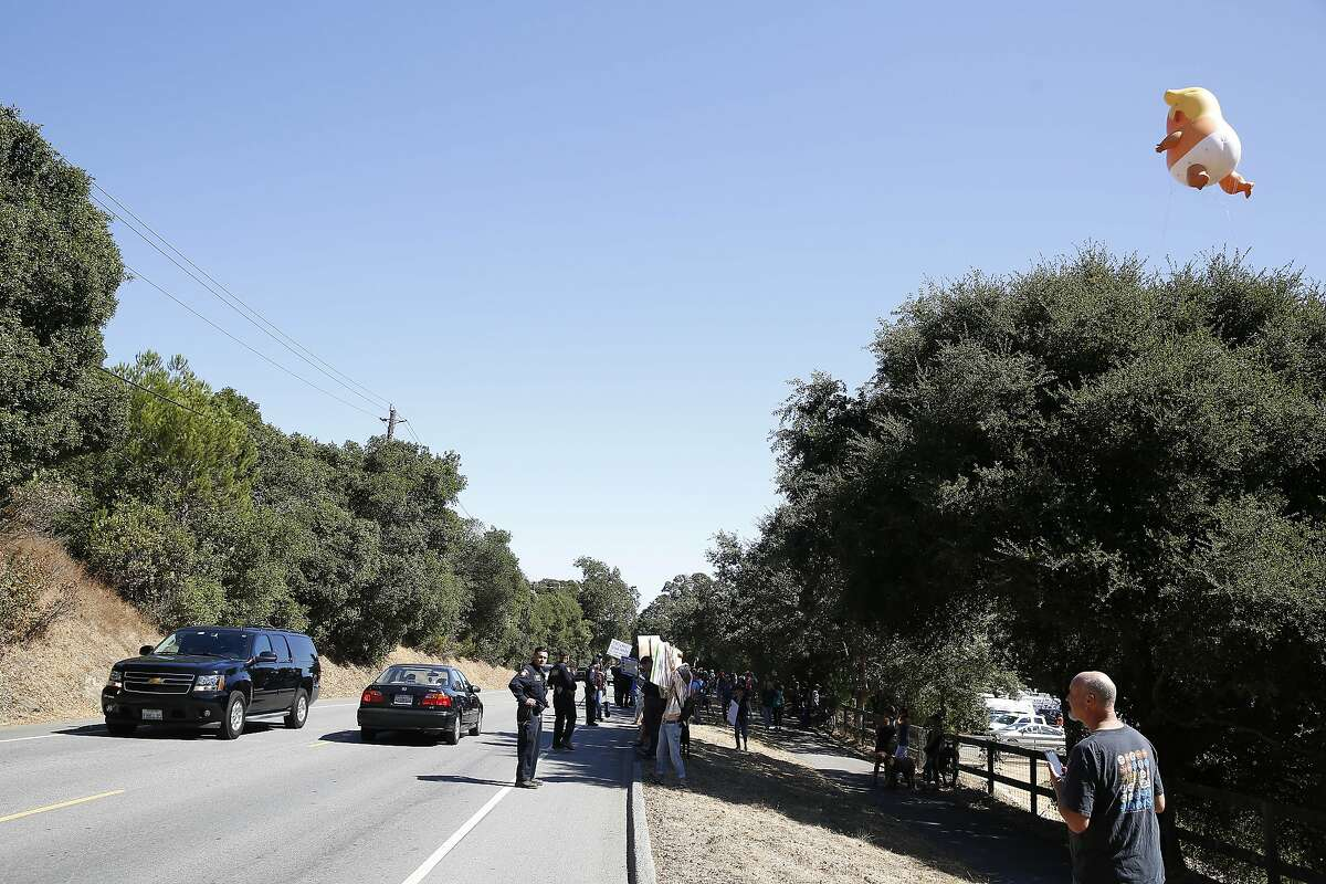 Protesters stand on Alpine Road as they wait for President Trump and his motorcade to pass on Tuesday, September 17, 2019 in Portola Valley, CA.