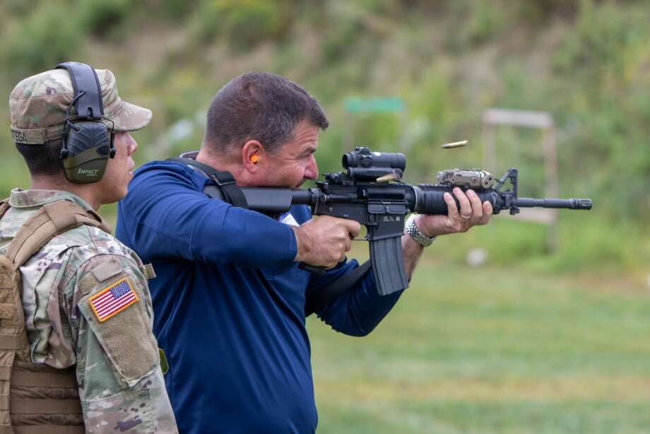 """Mathew Zink, the training director for the Bricklayers and Allied Craftworkers Union in Albany, N.Y. fires an M-4 carbine during a """"boss lift"""" at Camp Smith Training Site in Cortlandt Manor, N.Y. on Monday, Sept. 16, 2019 as New York Army National Guard Sgt. Omar Ortega, a member of the 1st Battalion 69th Infantry looks on..Twenty employers from the Albany, N.Y. area and Long Island visited Camp Smith Training Site to get a first hand look at New York Army National Guard training, including using electronic simulators and firing the M-4 and M-9, as part of the Employer Support of the Guard and Reserve program. ( NY Division of Military and Naval Affairs photo by NYG Specialist Michael T. Rehbaum) Photo: Provided By The NY National Guard"""