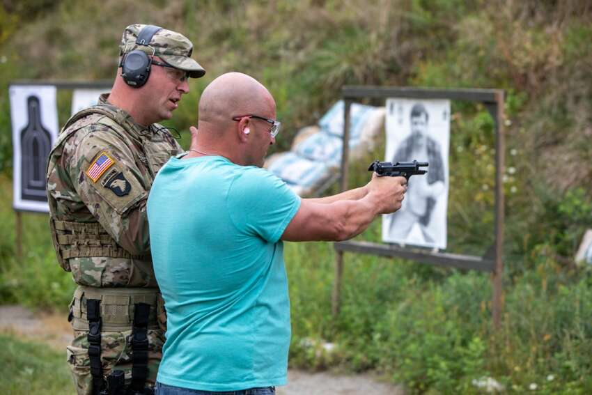 Bricklayers Union field representative Woody Miller gets tips on firing the M-9 pistol from New York Army National Guard Sgt. 1st Class Fredrick Goldackerduring a