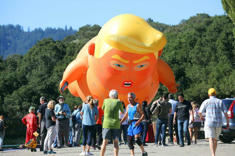 Protesters fly a balloon mocking President Donald Trump in Palo Alto, Calif., during Trump's visit to the state, Sept. 17, 2019. Trump has made California's homelessness crisis a key talking point ahead of his trip there. (Jim Wilson/The New York Times) Photo: Jim Wilson, NYT