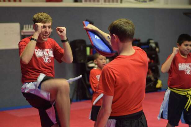 Inspiring Possibilities martial arts student Matthew Guettler (left) practices a kick with instructor Ben White while Jayden Charles and Raymond Higuera practice in the background.