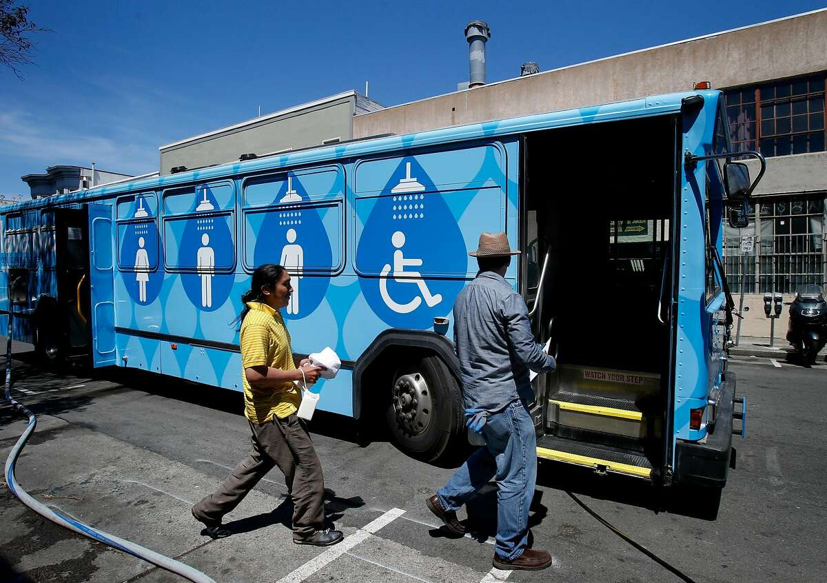 Lava Mae employee Michael McMorrow (right) led Jose Poot to his shower stall in the bus Tuesday June 24, 2014 in San Francisco, Calif. Lava Mae, the program that is turning old MUNI buses into showers for homeless people. began their test run in front of the Mission Neighborhood Resource Center.