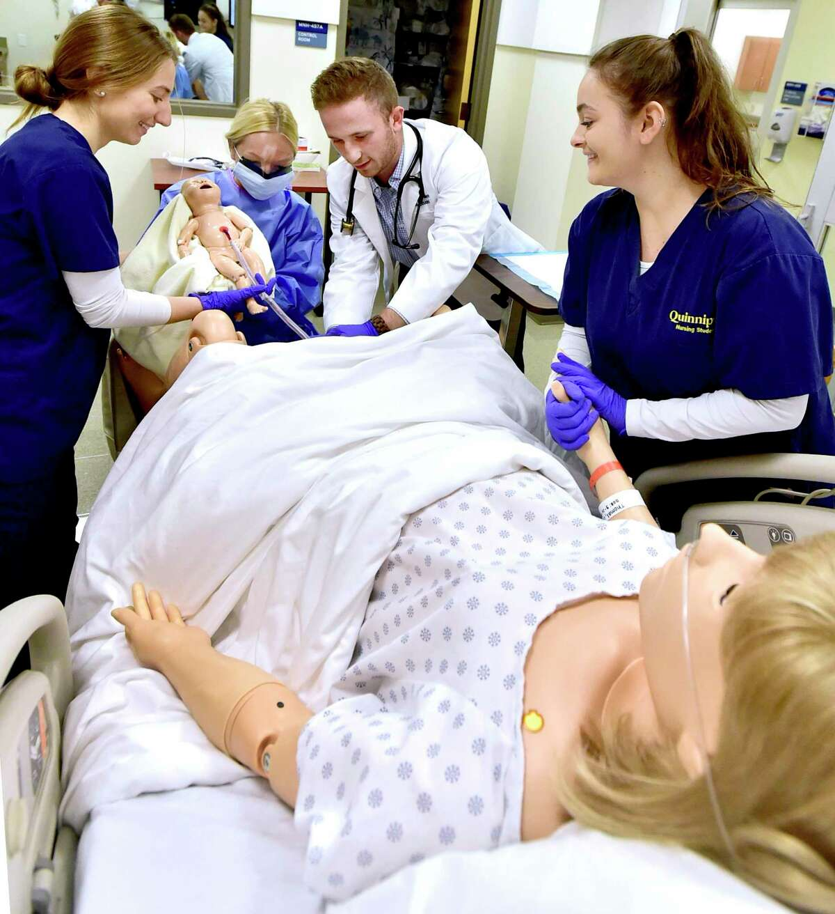 """During inter-professional training, Quinnipiac University physician assistant graduate students Connor Moore, third from left, and Ashley Ryan, second from left, and QU nursing students Kiya Ruggiero, right, and Alicia Ricci, left, deliver a simulated baby using a Guamard Scientific """"Noelle"""" birthing mannikin as Quinnipiac University undergraduate nursing students and physician assistant graduate students work with live """"standardized patient"""" actors and several simulation manikins at the Quinnipiac University Center for Medicine, Nursing and Health Sciences simulation lab on the North Haven Campus. The manikins include a life-size wirelessly controlled man known as the SimMan 3G, a realistically proportioned 25-week preterm infant manikin known as Premature Anne, and a Pediatric Hal, touted as the world's most advanced pediatric patient simulator and the first capable of simulating lifelike emotions through dynamic facial expressions, movement and speech. The live """"standardized patient"""" actors are trained to act like patients or patients' family."""