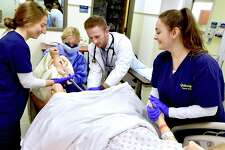 "During inter-professional training, Quinnipiac University physician assistant graduate students Connor Moore, third from left, and Ashley Ryan, second from left, and QU nursing students Kiya Ruggiero, right, and Alicia Ricci, left, deliver a simulated baby using a Guamard Scientific ""Noelle"" birthing mannikin as Quinnipiac University undergraduate nursing students and physician assistant graduate students work with live ""standardized patient"" actors and several simulation manikins at the Quinnipiac University Center for Medicine, Nursing and Health Sciences simulation lab on the North Haven Campus. The manikins include a life-size wirelessly controlled man known as the SimMan 3G, a realistically proportioned 25-week preterm infant manikin known as Premature Anne, and a Pediatric Hal, touted as the world's most advanced pediatric patient simulator and the first capable of simulating lifelike emotions through dynamic facial expressions, movement and speech. The live ""standardized patient"" actors are trained to act like patients or patients' family."