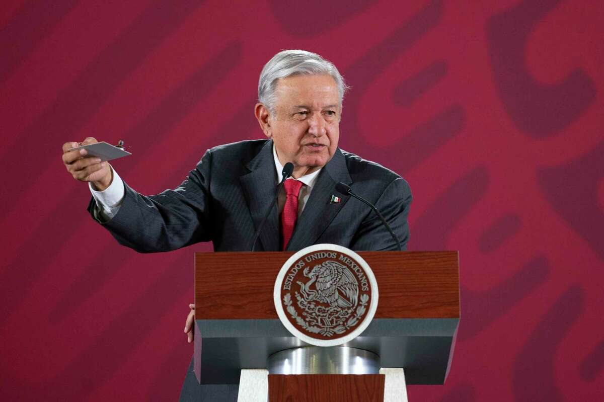 In this handout photo provided by Mexico's Presidential Press Office, Mexico's President Andres Manuel Lopez Obrador, holds a tiny camera he says was being used to spy on his meetings, during his morning news conference at the National Palace in Mexico City, Tuesday, Sept. 3, 2019. The president said