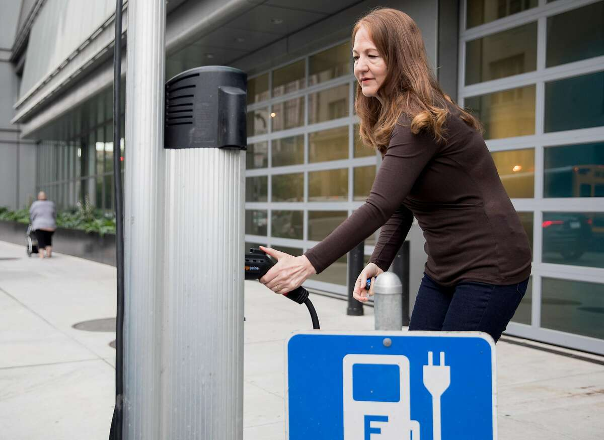 Amy Sinclair charges her all-electric vehicle at a public charging station near Polk Street and Golden Gate Avenue in San Francisco, Calif. Friday, August 30, 2019.
