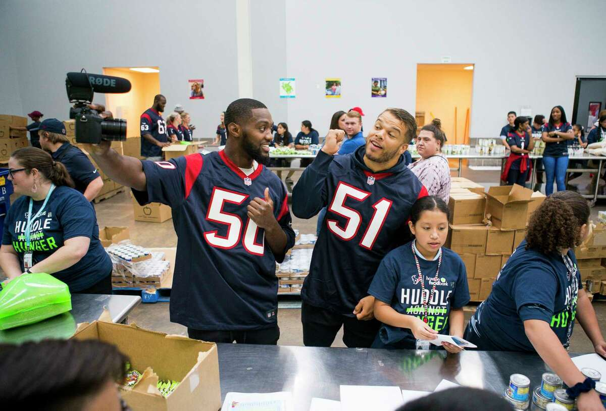 Houston Texans Tyrell Adams and Dylan Cole film a video while packing bags of food with students from YES Prep East End and other members of the Texans organization during a kickoff event for Huddle Against Hunger, a partnership between the Houston Texans and the Houston Food Bank, at the food bank's main facility in east Houston, Tuesday, Sept. 17, 2019. Huddle Against Hunger is a curriculum designed to teach school students about hunger and poverty.