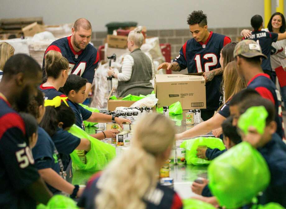 Houston Texans tackle Max Scharping and wide receiver Kenny Stills pack bags of food with students from YES Prep East End and other members of the Texans organization during a kickoff event for Huddle Against Hunger, a partnership between the Houston Texans and the Houston Food Bank, at the food bank's main facility in east Houston, Tuesday, Sept. 17, 2019. Huddle Against Hunger is a curriculum designed to teach school students about hunger and poverty. Photo: Mark Mulligan, Staff Photographer / © 2019 Mark Mulligan / Houston Chronicle