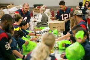 Houston Texans tackle Max Scharping and wide receiver Kenny Stills pack bags of food with students from YES Prep East End and other members of the Texans organization during a kickoff event for Huddle Against Hunger, a partnership between the Houston Texans and the Houston Food Bank, at the food bank's main facility in east Houston, Tuesday, Sept. 17, 2019. Huddle Against Hunger is a curriculum designed to teach school students about hunger and poverty.