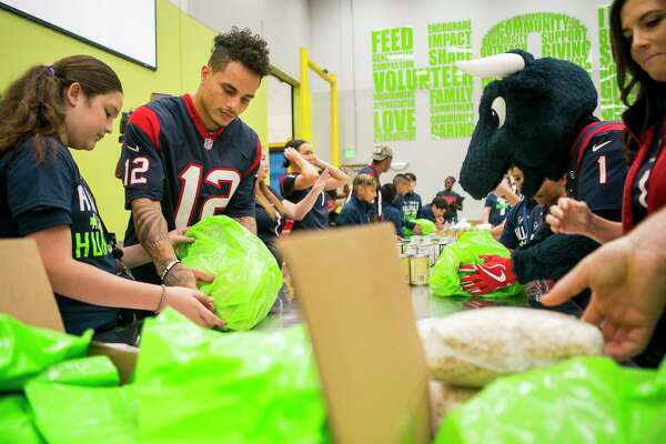 Texans wide receiver Kenny Stills learns to pack bags of food to give away with students from YES Prep East End and members of the Houston Texans organization during a kickoff event for Huddle Against Hunger, a partnership between the Houston Texans and the Houston Food Bank, at the food bank's main facility in east Houston, Tuesday, Sept. 17, 2019. Huddle Against Hunger is a curriculum designed to teach school students about hunger and poverty.
