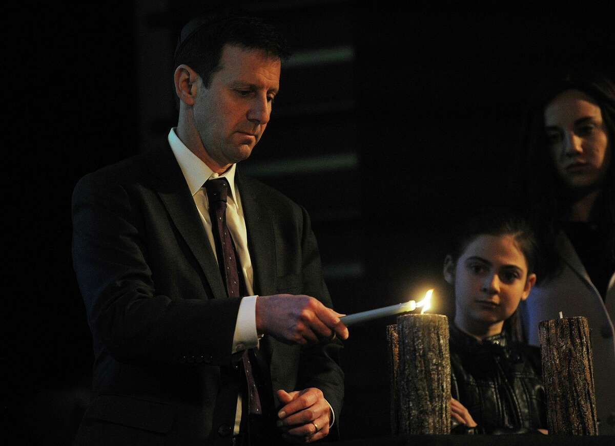 Connecticut Director of the Anti-Defamation League Steve Ginsburg lights a candle during a service honoring victims of the Pittsburgh synagogue shooting at the Klein Memorial Auditorium in Bridgeport, Conn. on Sunday, Oct. 28, 2018.