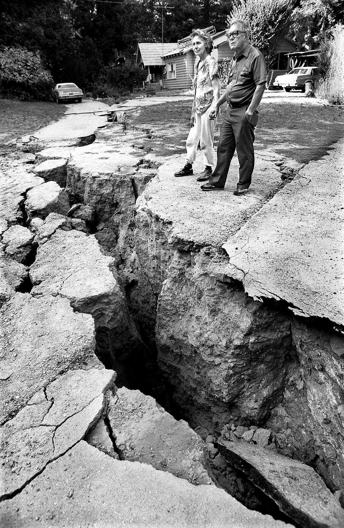 John and Freda Tranberger stand by a huge crack that opened up in their front yard after the Loma Prieta earthquake struck.