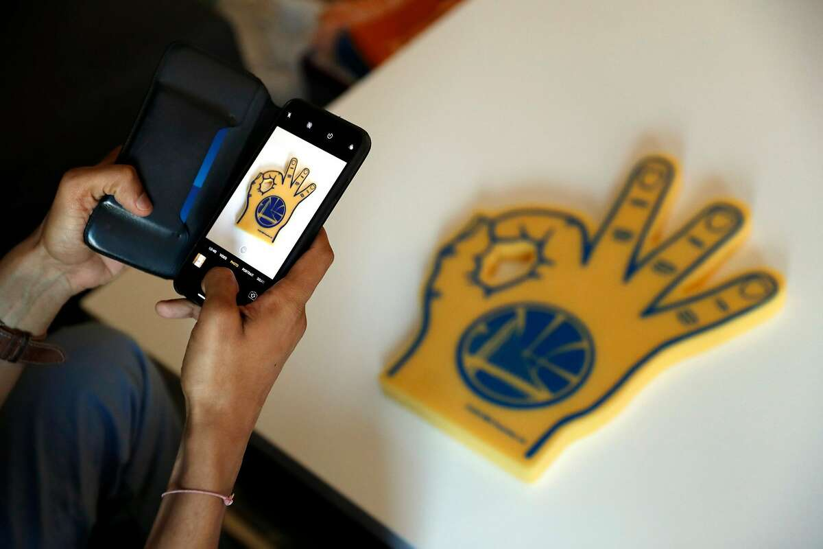 Shreyans Parekh photographs a Golden State Warriors' foam hand as he prepares to put it up for sale on Mercari at his residence in Foster City, Calif., on Thursday, September 12, 2019.