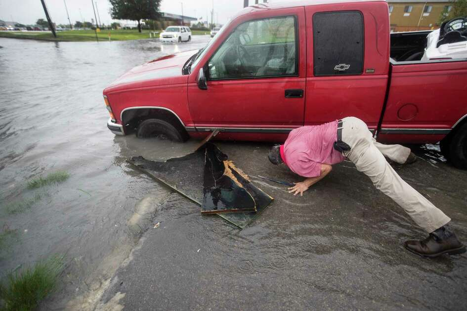 Felipe Morales works on getting his truck out of a ditch filled with high water along Rowlett Road during a rain storm stemming from rain bands spawned by Tropical Storm Imelda on Tuesday, Sept. 17, 2019, in Houston. He was able to get help when a man with a truck helped pull him from the ditch.