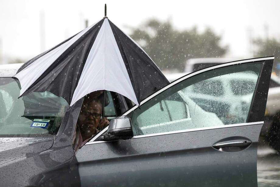 A woman closes her umbrella after getting into her car during a rain storm stemming from rain bands spawned by Tropical Storm Imelda near I-45 and Almeda-Genoa on Tuesday, Sept. 17, 2019, in Houston. Photo: Brett Coomer, Staff Photographer / © 2019 Houston Chronicle