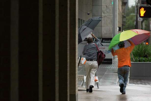 Pedestrians hold on to their umbrellas while crossing Fanning and Polk Streets as Tropical Storm Imelda is making its way across the Houston area during rush hour on Tuesday, Sept. 17, 2019, in downtown Houston.