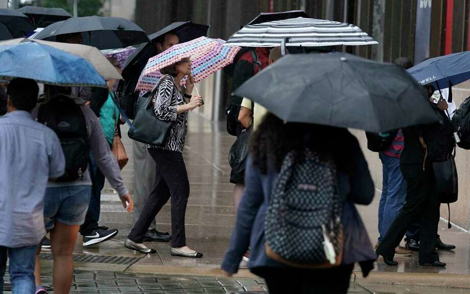 Afternoon rush hour commuters wait in the rain at a bus stop on Louisiana St. at the corner of Capitol St. downtown Tuesday, Sept. 17, 2019, in Houston.  Substantial rainfall is expected as Tropical Storm Imelda moves through the region. Photo: Melissa Phillip, Staff Photographer / © 2019 Houston Chronicle