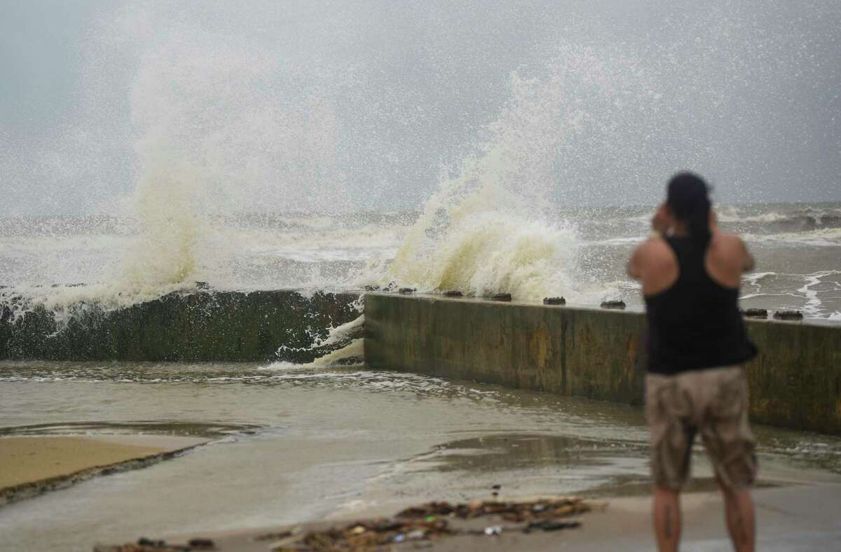 A women takes a photo of waves washing over the seawall near Rollover Pass on the Bolivar Peninsula Tuesday afternoon. Photo taken on Tuesday, 09/17/19. Ryan Welch/The Enterprise