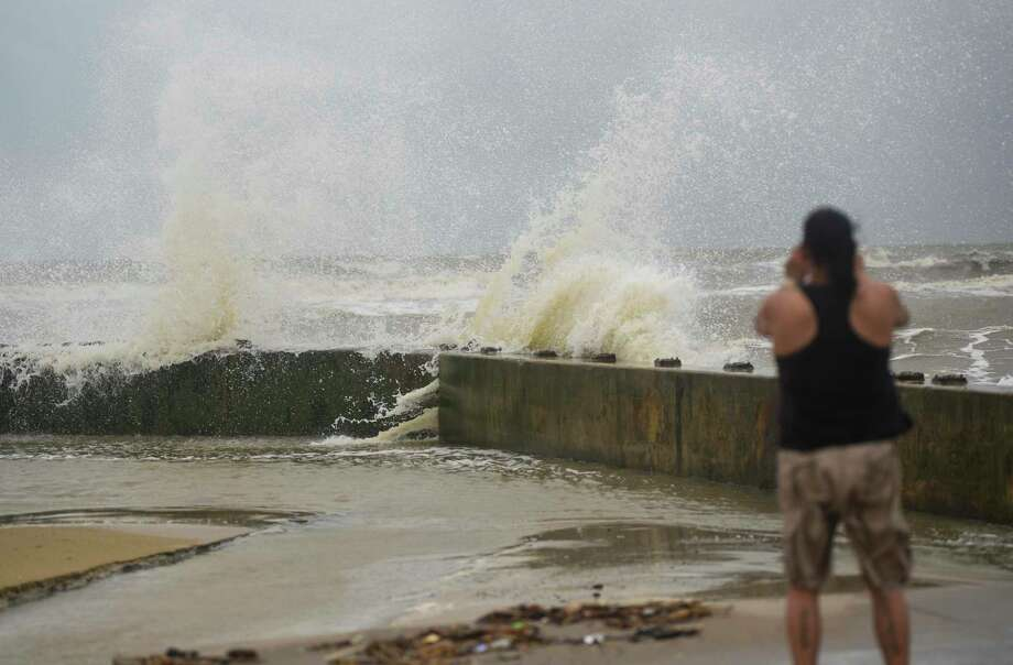 A women takes a photo of waves washing over the seawall near Rollover Pass on the Bolivar Peninsula Tuesday afternoon. Photo taken on Tuesday, 09/17/19. Ryan Welch/The Enterprise Photo: Ryan Welch, Beaumont Enterprise / The Enterprise / © 2019 Beaumont Enterprise