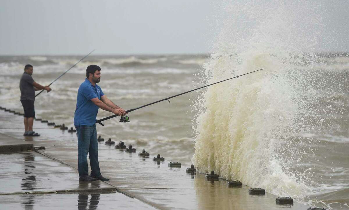 Two men fish on Rollover Pass as waves crash on to the seawall they are standing on in the Bolivar Peninsula Tuesday afternoon. Photo taken on Tuesday, 09/17/19. Ryan Welch/The Enterprise