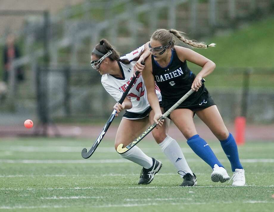 Bella Carrozza (left) battles a Darien player for control of the ball. Photo: Scott Mullin / For Hearst Connecticut Media / Scott Mullin ownership