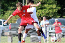 Evan Dugger of Alton (14) fends off Edwardsville's JT Watson during Tuesday's game at Alton High. Edwardsville won 3-1.