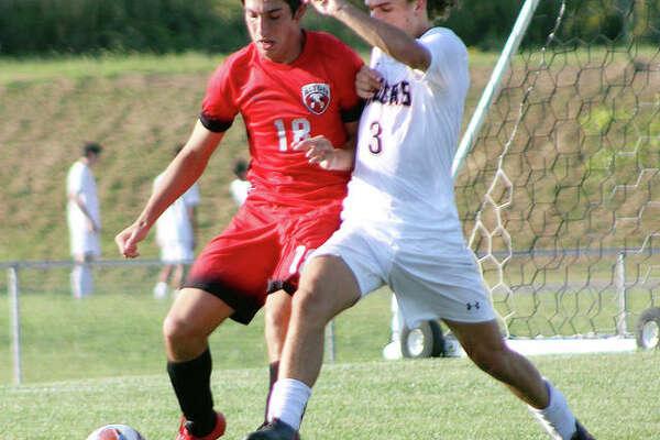 Edwardsville's Kadin Lieberman (3) and Alton's Justin Davison battle for the ball during Monday's game at Alton High School.