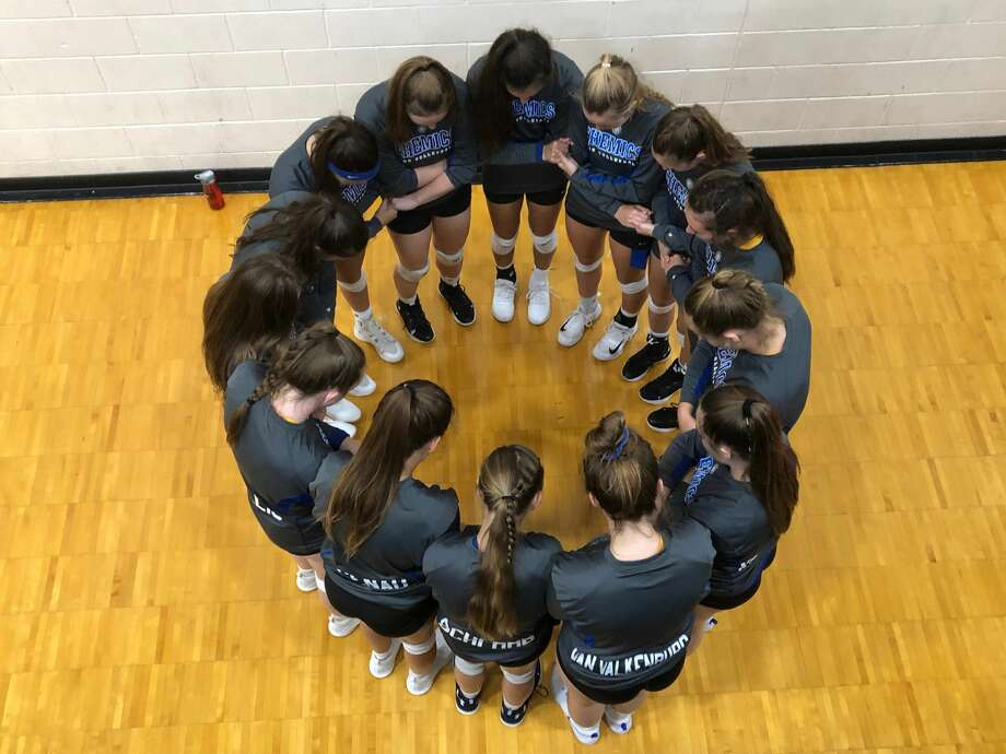 Midland High's volleyball team gathers in a circle to pray before Tuesday's match at Mount Pleasant. Photo: Photo Provided