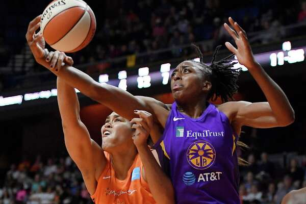 The Sun's Brionna Jones, left, and the Sparks' Nneka Ogwumike reach for the ball during the first half of their playoff game on Tuesday in Uncasville.