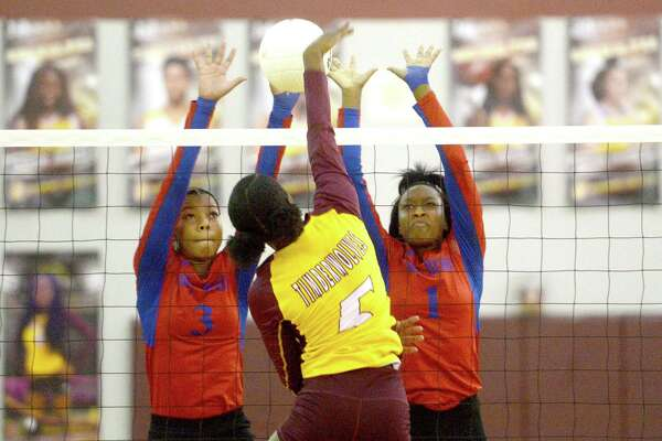 Beaumont United's Halee Simon spikes the ball as West Brook's LaRobyn Ellis (left) and ZaNya Alexander defend at the net during their volleyball match-up Tuesday at United. Photo taken Tuesday, September 17, 2019 Kim Brent/The Enterprise