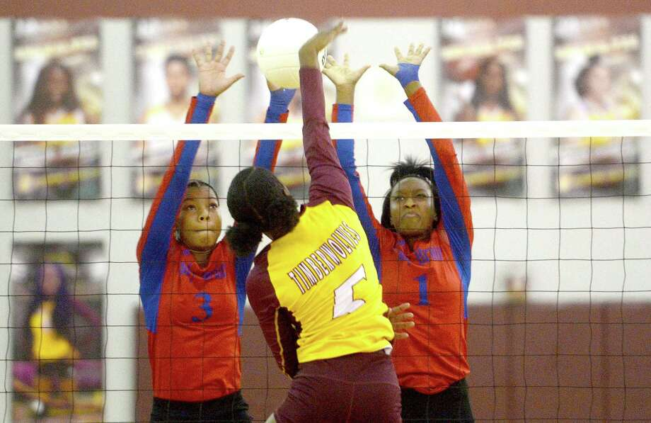 Beaumont United's Halee Simon spikes the ball as West Brook's LaRobyn Ellis (left) and ZaNya Alexander defend at the net during their volleyball match-up Tuesday at United. Photo taken Tuesday, September 17, 2019 Kim Brent/The Enterprise Photo: Kim Brent / The Enterprise / BEN