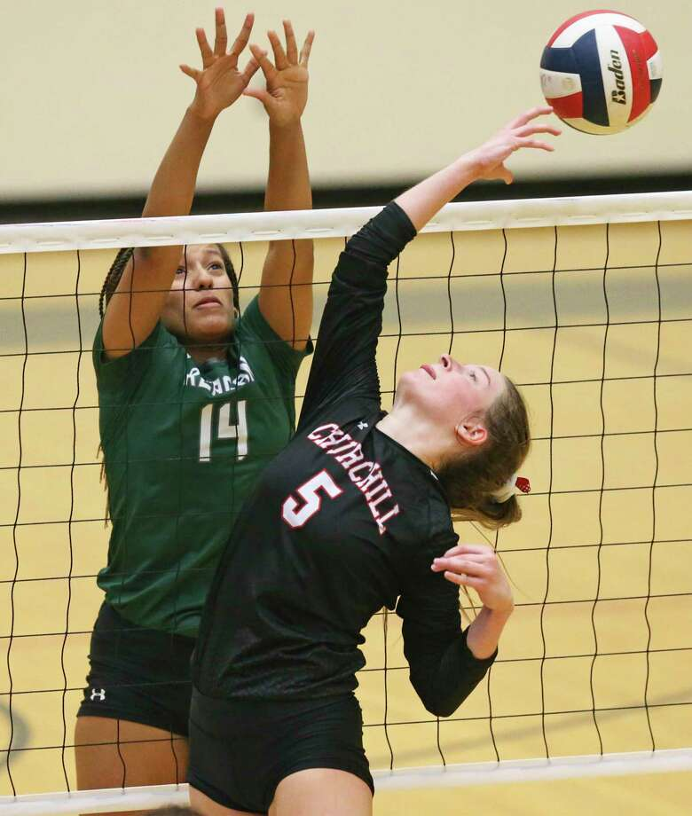Emma Sevening flips the ball backward to get away from Rattler defender Kiana Mond as Reagan beats Churchill 3-0 in volleyball at Littleton Gym on Sept. 17, 2019. Photo: Tom Reel, Staff / Staff Photographer / 2019 SAN ANTONIO EXPRESS-NEWS