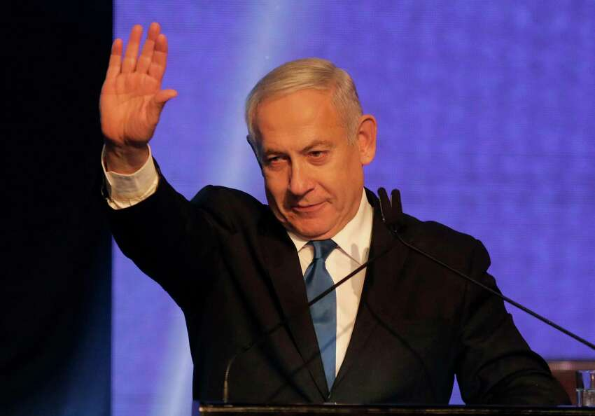 Israeli Prime Minister Benjamin Netanyahu waves as he addresses supporters at his Likud party's electoral campaign headquarters early on September 18, 2019. - Israeli Prime Minister Benjamin Netanyahu said he was waiting for results in the country's general election, but that he was prepared for negotiations to form a