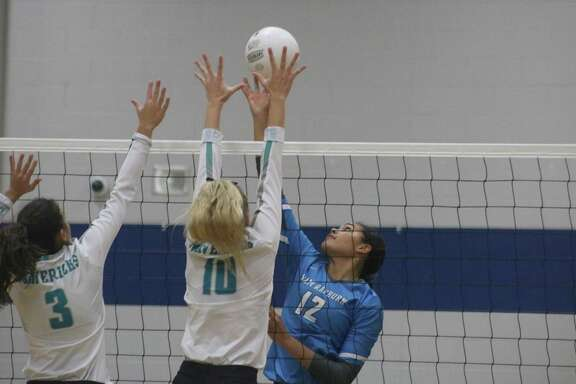 Memorial's Sarah Curtis (3) and Brandi Hemminger attempt to stop the work of Torrie Woods at the net during Game 2 action Tuesday night.