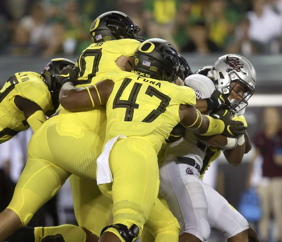 Oregon linebacker Mase Funa (center) helps bring down Montana running back Marcus Knight during the Ducks' 35-3 win in Eugene last Saturday. Photo: Chris Pietsch / Associated Press