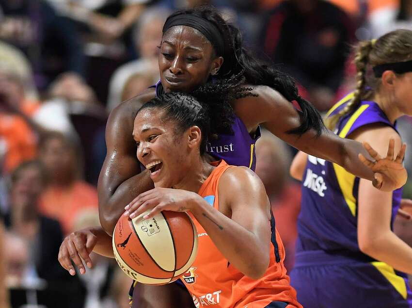 Connecticut Sun's Alyssa Thomas is pressured by Los Angeles Sparks' Chiney Ogwumike during the second half of Game 1 of a WNBA basketball playoff game, Tuesday, Sept. 17, 2019, in Uncasville, Conn. (AP Photo/Jessica Hill)