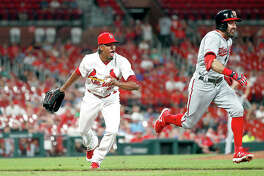 The Nationals' Adam Eaton, right, heads to first base with a single on a softly hit ground ball, as Cardinals pitcher Genesis Cabrera is late tossing the ball to first in the ninth inning of Tuesday night's game in St. Louis.