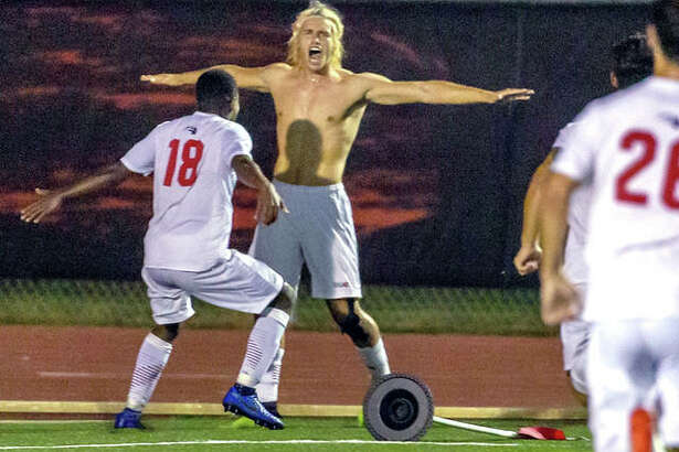 SIUE's Jorge Gonzalez, after ripping off his jersey, celebrates with teammate Vincent Jackson II (18) Tuesday night after scoring the game-winning overtime goal in the Cougars 2-1 win over Butler at Korte Stadium.