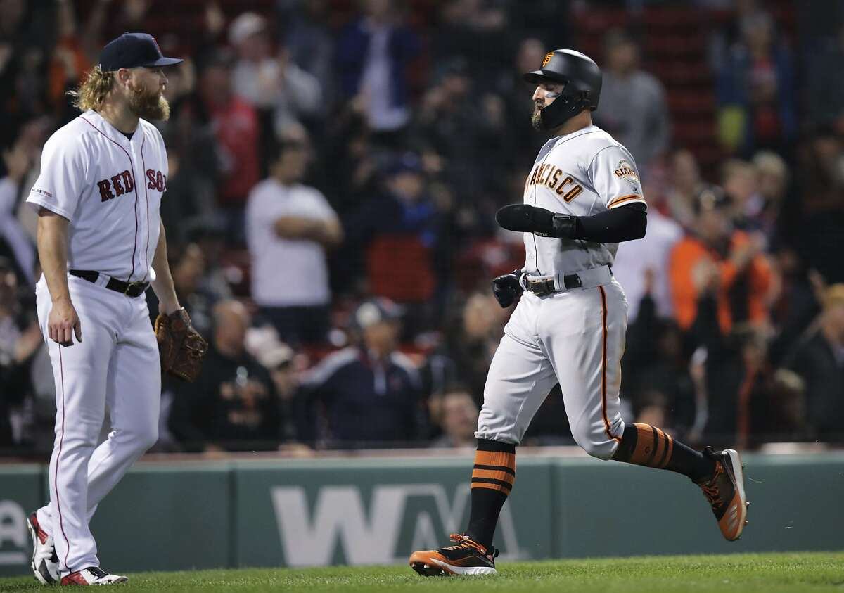 San Francisco Giants' Kevin Pillar, right, scores on a double by Brandon Crawford off Boston Red Sox relief pitcher Andrew Cashner, left, during the 13th inning of a baseball game at Fenway Park in Boston, Tuesday, Sept. 17, 2019. (AP Photo/Charles Krupa)