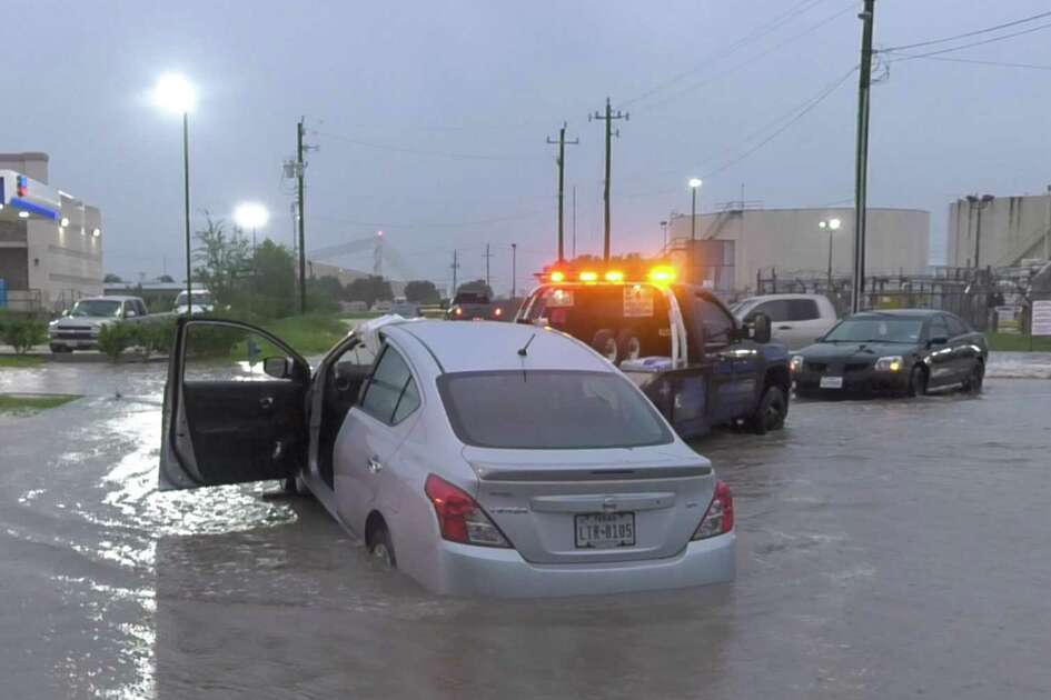 Wrecker drivers pull stranded motorists and their cars out of the flooded roadway on Monroe Boulevard near Hobby Airport Wednesday, Sept. 18, 2019, in Houston.